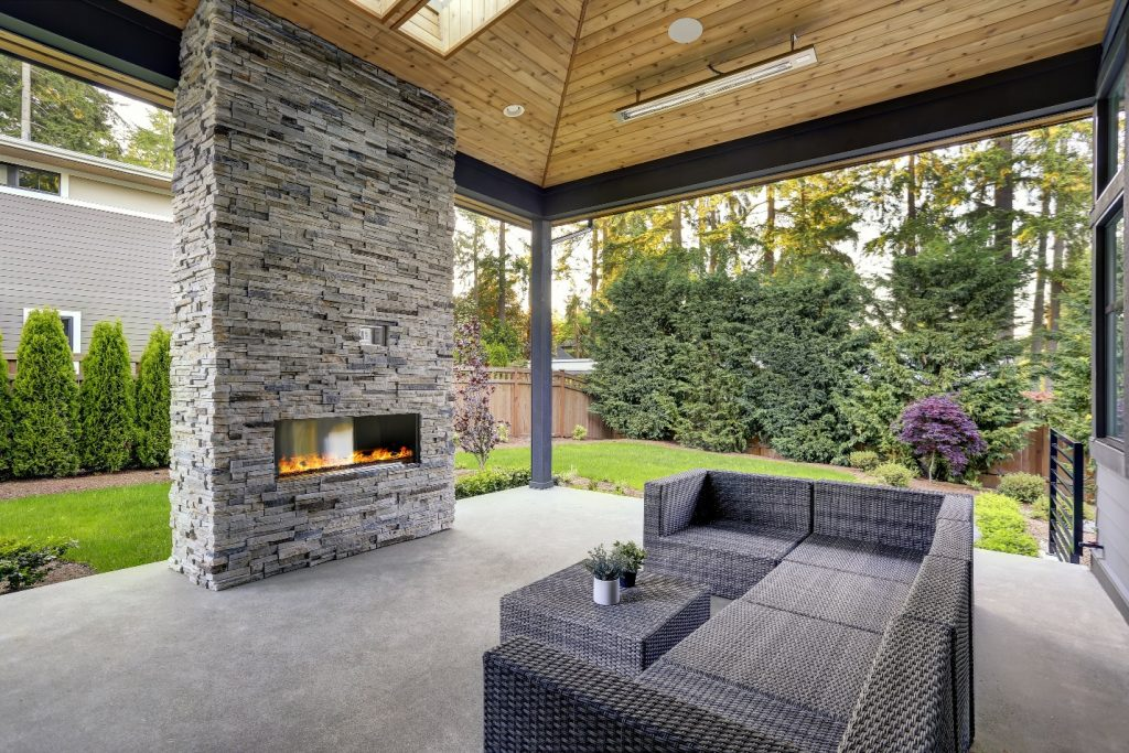 modern deck with stone fireplace and wooden ceiling