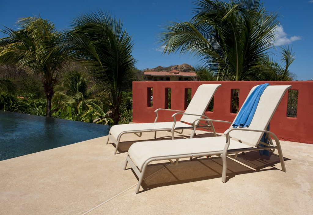 lounge chairs with blue towel on a pool deck
