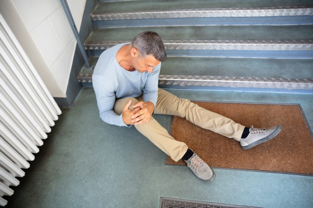 older man sitting at stairs after falling