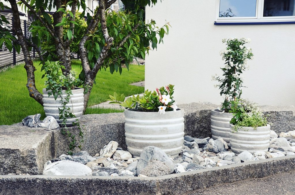 Stone garden arrangement at house entrance with green and white plants