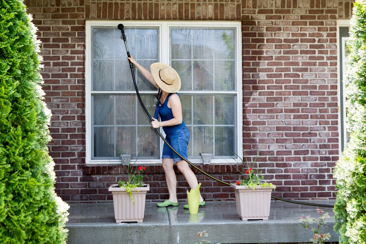 Housewife washing the windows of her house with a hose