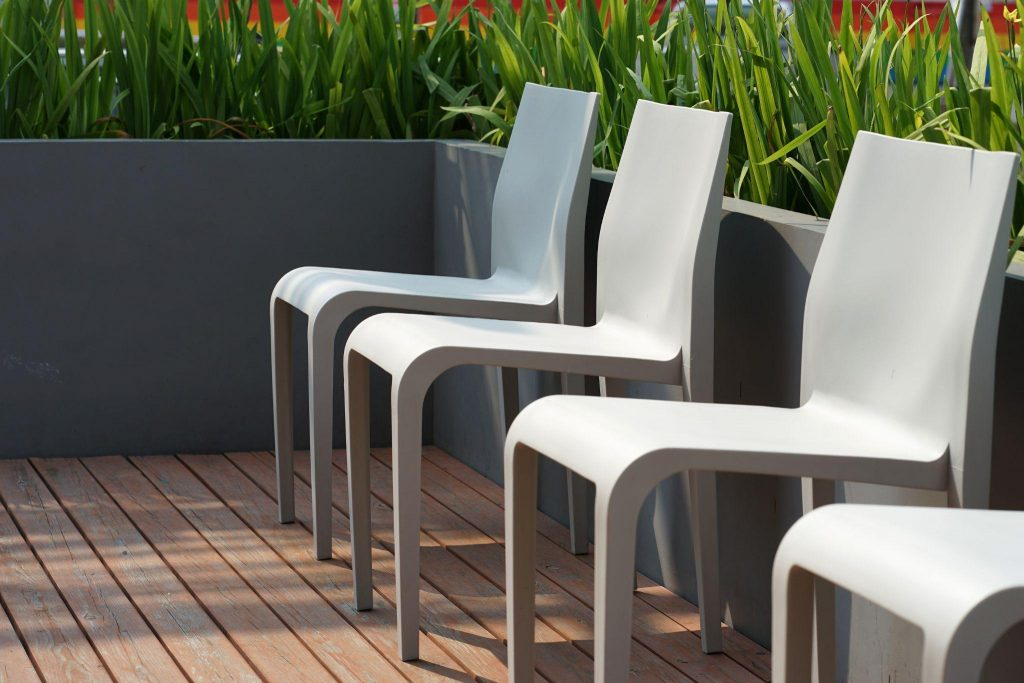 plastic chairs on the timber terrrace with planter box background outdoor