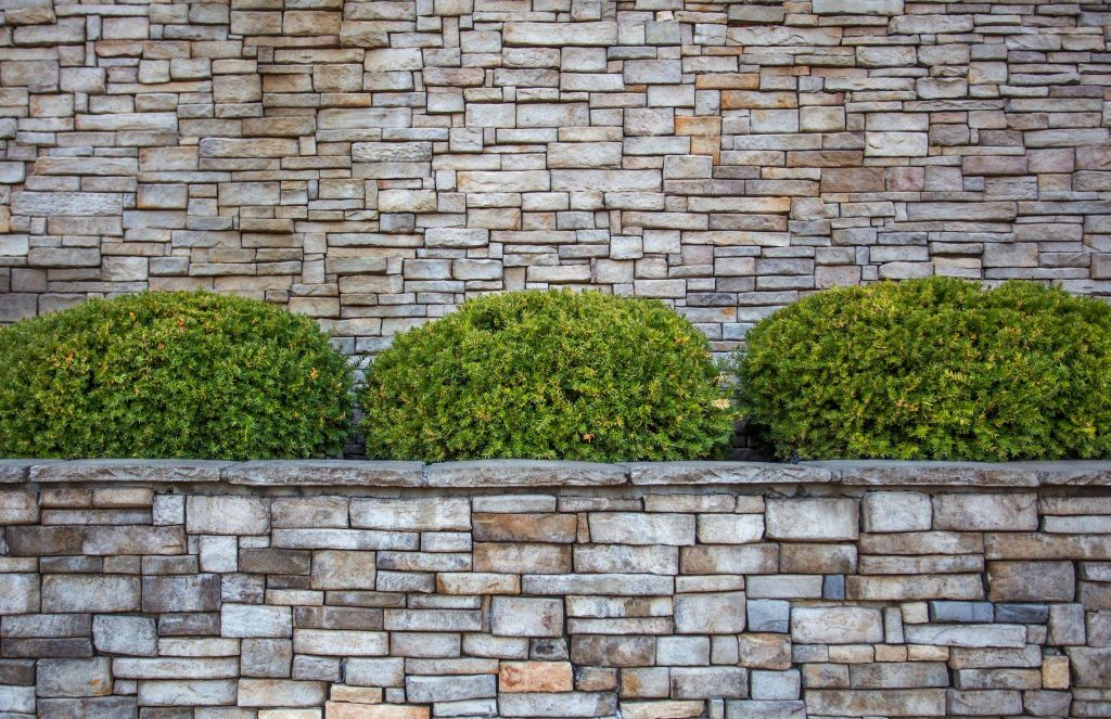 Rounded green shrubs in planter box against a gray and brown brick wall