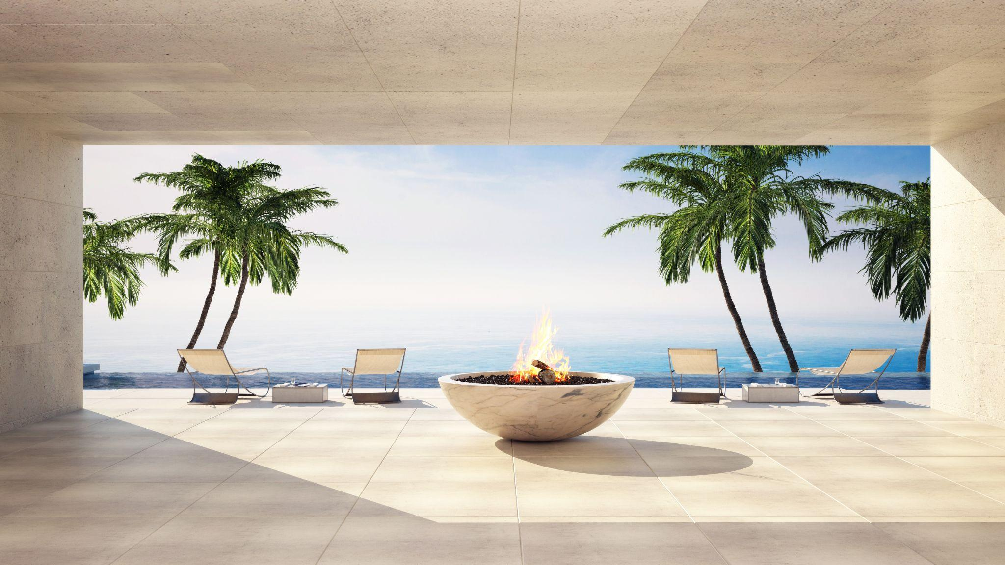 Open patio in a luxury villa overlooking the sea with palm trees and feature burning flame